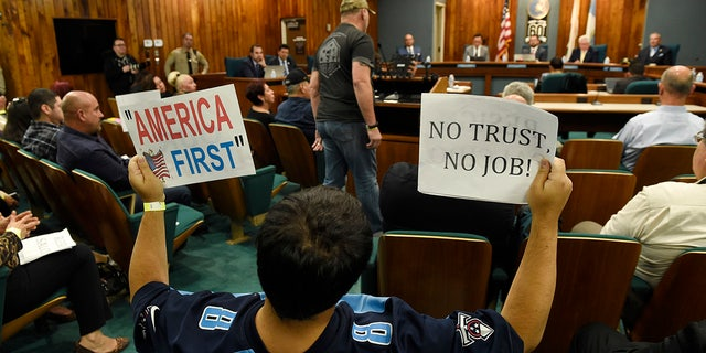 Jamie Park of Pico Rivera, Calif., holds up signs during a city council meeting at Pico Rivera City Hall on Tuesday.