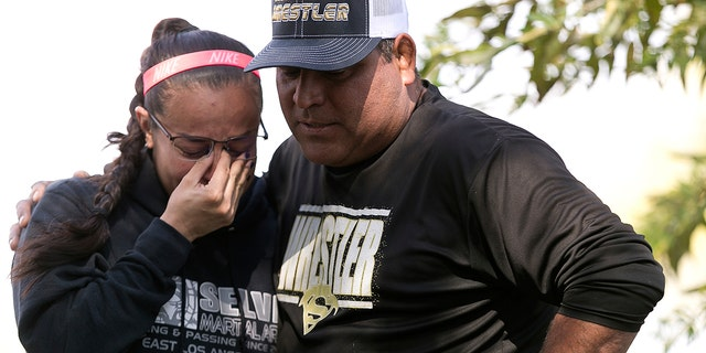 Wrestling coach Ray Castellanos, right, and assistant coach, Monique Cabrera, left, stand at the site where South El Monte High School student, Jeremy Sanchez, a 17-year-old was fatally stabbed by a teenage friend, in South El Monte, Calif.
