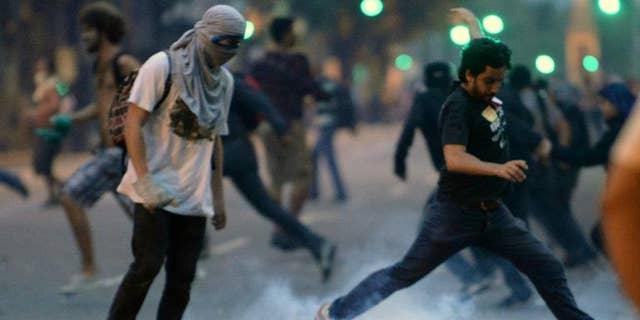 A demonstrator kicks a tear gas grenade during a protest by teachers in Rio de Janeiro, Brazil, on October 1, 2013