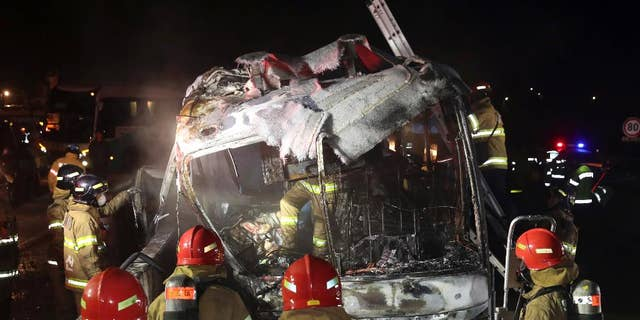 South Korean firefighters check a burned out bus on the Gyeongbu Expressway near the southeastern city of Ulsan, South Korea, Friday, Oct. 14, 2016. Twenty people, including the driver, were on the bus when it smashed into the guardrail and caught fire on the expressway, officials said. (Kim Yong-tae/Yonhap via AP) KOREA OUT