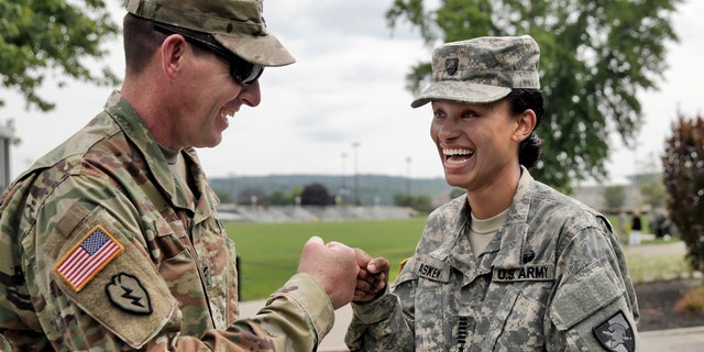 Cadet Simone Askew, of Fairfax, Va., right, talking with Brigade Tactical Officer Col. Brian Reed, has been selected first captain of the Corps of Cadets for the upcoming academic year at the U.S. Military Academy in West Point, NY, Monday, Aug. 14, 2017