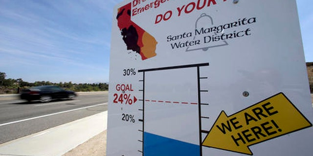 In this July 2, 2015 file photo, cars, in Rancho Santa Margarita, Calif., drive by a sign encouraging residents to save water.
