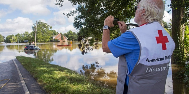 James Hennessy, a Red Cross mental health volunteer from Tallahassee, Florida, takes a photo of Old Jefferson Highway which he was hoping to cross to reach Baton Rouge in Prairieville, La.