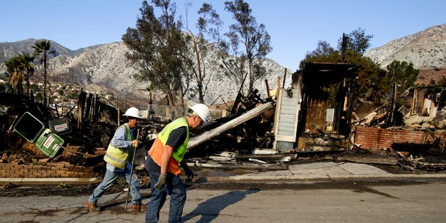 Workers from the Los Angeles Dept. of Water and Power walk past a home destroyed by wildfire along Via San Anselmo in the Sylmar area of Los Angeles Wednesday, Dec. 6, 2017.
