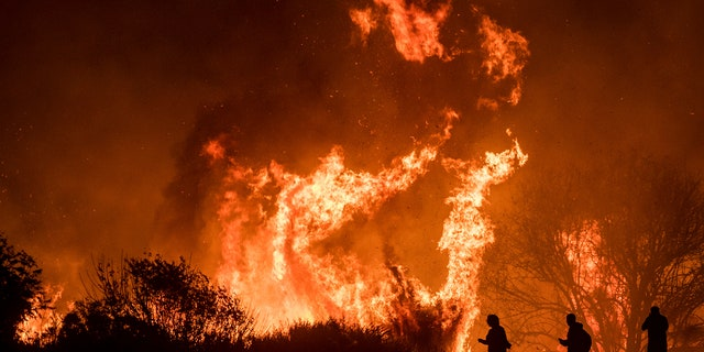 Motorists on Highway 101 watch flames from the Thomas fire leap above the roadway north of Ventura, Calif., on Wednesday, Dec. 6, 2017.