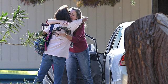 Two women embrace outside Rancho Tehama Elementary School, where a gunman opened fire Tuesday, Nov. 14, 2017, in Corning, Calif.