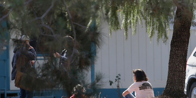 A woman and a child sit by an elementary school where a gunman opened fire in the community of Rancho Tehama Reserve in Corning, Calif., Tuesday, Nov. 14, 2017.