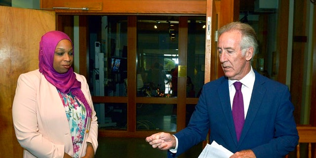 Democratic Rep. Richard Neal flips a coin to determine speaking order as challenger Tahirah Amatul-Wadud looks on before their primary debate at WGBY TV in Springfield, Mass., Thursday, Aug. 30, 2018.