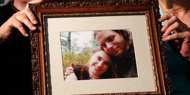 Foto tomada el 4 de junio del 2014 en Stewartstown, Pensilvania en que familiares sujetan un retrato del canadiense Joshua Boyle y su esposa la estadounidense Caitlan Coleman, quienes han sido puestos en libertad en Pakistán el 11 de octubre del 2017 tras ser secuestrados cinco años atrás.   (AP Photo/Bill Gorman, File)