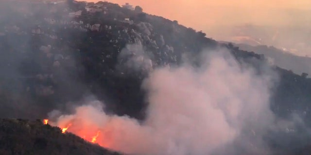 In this image taken from video provided by the Santa Barbara County Fire Department, a wind driven spot fire burns on the west side below Gibraltar Road as smoke from a wildfire fills the air in Santa Barbara, Calif., Saturday, Dec. 16, 2017.