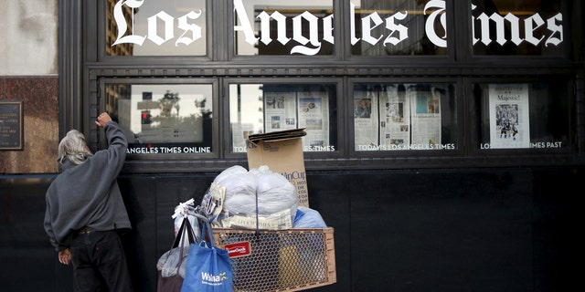 A homeless man reads the Los Angeles Times in the window of the building of Los Angeles Times newspaper in Los Angeles.