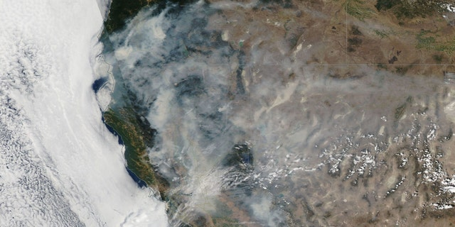 An image captured by NASA shows wildfires raging over California and Oregon.