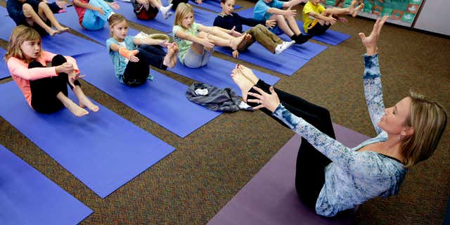 Dec. 11, 2012: Yoga instructor Kristen McCloskey, right, leads a class of third graders at Olivenhain Pioneer Elementary School in Encinitas, Calif.