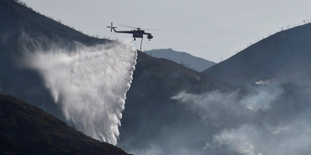 In this photo provided by the Santa Barbara County Fire Department, a Sikorsky S-64 Skycrane makes a water drop on hot spots along the hillside east of Gibraltar Road in Santa Barbara, Calif., Sunday morning, Dec. 17, 2017.