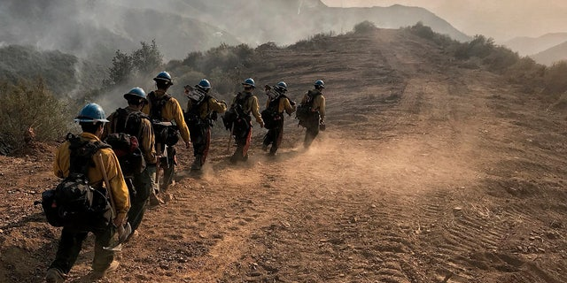In this photo provided by the Santa Barbara County Fire Department, U.S. Forest Service Hot Shot crew members from Ojai, Calif., head down a fire break to work off E. Camino Cielo in Santa Barbara, Calif., Sunday morning, Dec. 17, 2017.