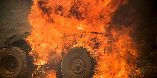 Flames from a wildfire consume an all-terrain vehicle near Oroville, Calif., on Saturday, July 8, 2017.