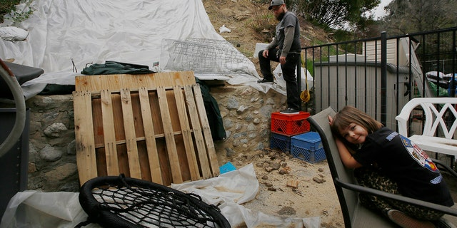 Andrew Joos-Visconti works to protect his back yard from the upcoming rains with a plastic tarp, in the Sun Valley area of Los Angeles Tuesday, March 20, 2018. At right, his daughter, Scarlett, 4.