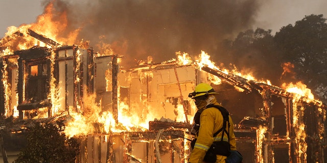 A firefighter monitors a house burning in Santa Rosa, Calif., Monday, Oct. 9, 2017.
