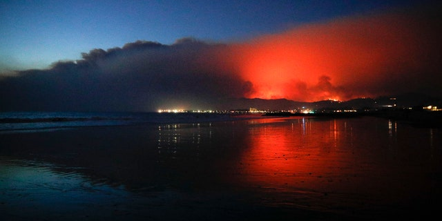 A wildfire continues to burn as its red glow is reflected on the beach on Tuesday.