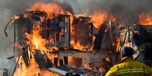 A wildfire consumes a home in Ventura, Calif.