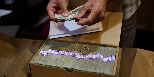 In this June 27, 2017, file photo, Jerred Kiloh, owner of the Higher Path medical marijuana dispensary, prepares his monthly tax payment, $40,131.88 in cash in Los Angeles.