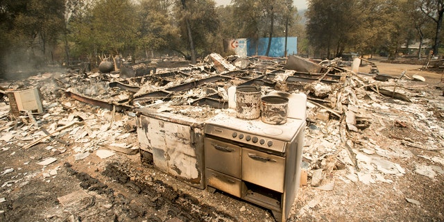A stove stands in front of a structure leveled by a wildfire near Oroville, Calif., on Saturday, July 8, 2017. Residents were ordered to evacuate from several roads in the rural area as flames climbed tall trees.