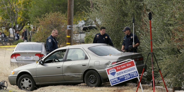California Highway Patrol Officers inspect one of the vehicles involved when a gunman went on a shooting rampage at the Rancho Tehama Reserve, near Corning, Calif., Tuesday, Nov. 14, 2017.
