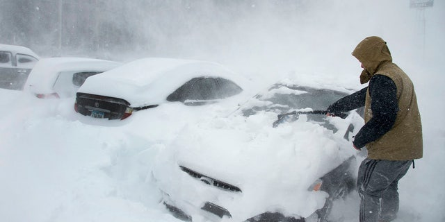 Heavy winds blow snow as Ryan Foster, 25, scrapes snow from his car in the parking lot where he lives at the Donner Summit Lodge in Norden on Thursday, March 1, 2018, near Donner Summit, Calif.