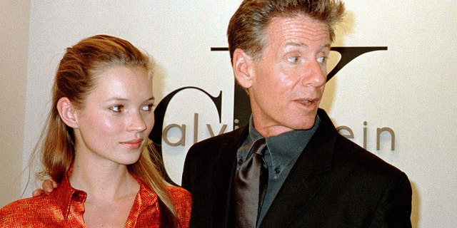 International model Kate Moss (L) and designer Calvin Klein gather for the opening of his first dedicated designer store in Hong Kong September 5, 1996.
