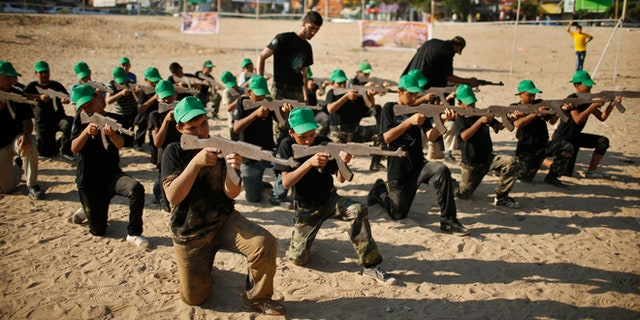Palestinian boy Mahmoud Haniyeh (front, 1st L), 13, aims a wooden gun during a military-style exercise at a summer camp organized by the Hamas movement in Gaza City June 17, 2013. Tens of thousands of children from the Gaza Strip spend at least part of their holidays in special summer camps, arranged around a wide array of activities. Some, organised by the United Nations, offer sports, art and dance classes. Others, laid on by Gaza's Islamist rulers Hamas, include fun and games, while seeking to reinforce religious values and awareness of the conflict with Israel. Picture taken June 17, 2013. REUTERS/Mohammed Salem (GAZA - Tags: POLITICS EDUCATION SOCIETY)ATTENTION EDITORS: PICTURE 08 OF 31 FOR PACKAGE 'ON HOLIDAY IN GAZA'S SUMMER CAMPS'. TO FIND ALL IMAGES SEARCH 'SUMMER CAMPS' - RTX10ZZR