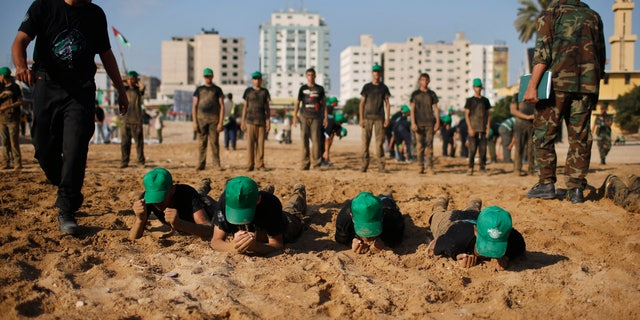 Palestinian boys crawl during a military-style exercise at a summer camp organized by the Hamas movement in Gaza City June 17, 2013. Tens of thousands of children from the Gaza Strip spend at least part of their holidays in special summer camps, arranged around a wide array of activities. Some, organised by the United Nations, offer sports, art and dance classes. Others, laid on by Gaza's Islamist rulers Hamas, include fun and games, while seeking to reinforce religious values and awareness of the conflict with Israel. Picture taken June 17, 2013. REUTERS/Mohammed Salem (GAZA - Tags: POLITICS EDUCATION SOCIETY)   ATTENTION EDITORS: PICTURE 09 OF 31 FOR PACKAGE 'ON HOLIDAY IN GAZA'S SUMMER CAMPS'. TO FIND ALL IMAGES SEARCH 'SUMMER CAMPS' - RTX10ZZQ