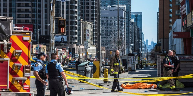 A body lies covered on the sidewalk in Toronto after a van mounted a sidewalk crashing into a number of pedestrians.