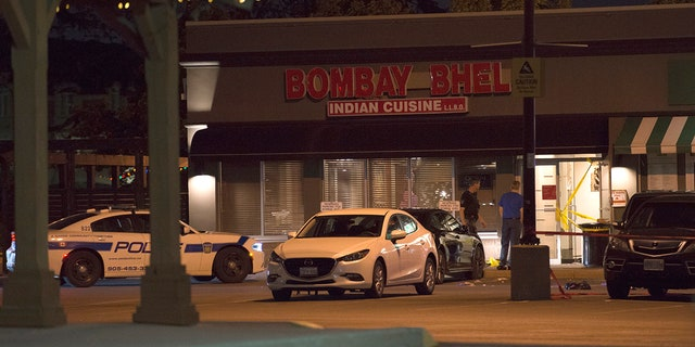 Police stand outside the Bombay Bhel restaurant in Mississauga, Canada Friday.