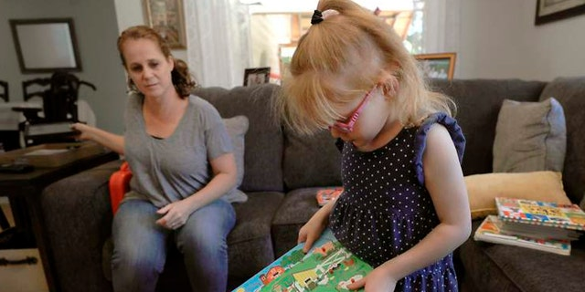 In this Monday, July 23, 2018, photo minutes before having a seizure, Brooke Adams, 5, plays with her toys with her mother, Jana at their home in Santa Rosa, Calif.