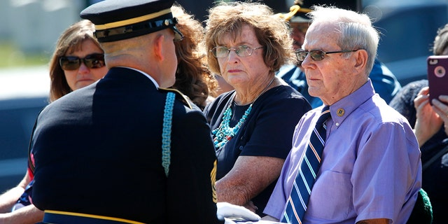 Wayne Brazeau, right, next to his wife Dorothy Brazeau, is handed the flag by 1st Sgt. Raymond Wrensch, left, during the burial service at Arlington National Cemetery on Tuesday in Arlington, Va., for Army Air Force Staff Sgt. John H. Canty.