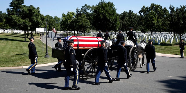 A horse drawn caisson carries the remains of Army Air Force Staff Sgt. John H. Canty, of Winsted, Conn., during his burial service at Arlington National Cemetery on Tuesday.