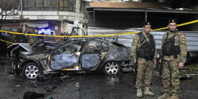 Officials stand in front of a car that was destroyed in a bombing in the southern port city of Sidon, Lebanon, Sunday, Jan. 14, 2018