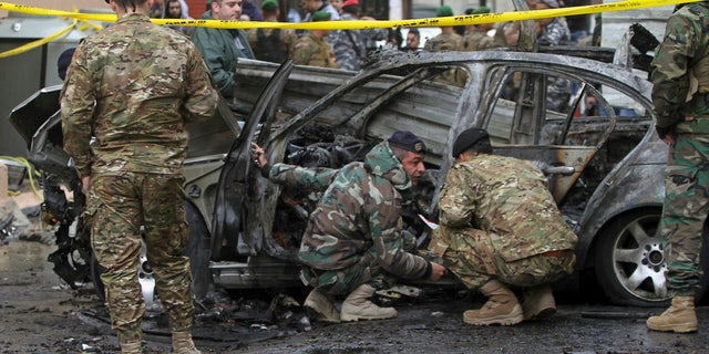 Officials examine a car that was destroyed in a bombing in the southern port city of Sidon, Lebanon, Sunday, Jan. 14, 2018