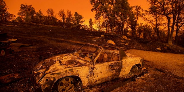 Cars scorched by the Carr Fire rest at a residence in Redding, Calif., on Friday, July 27, 2018