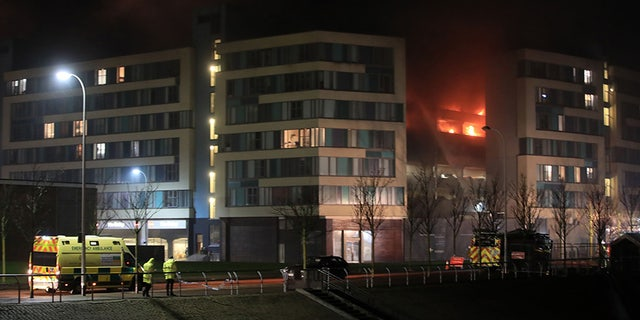 Emergency services attend the scene of a fire at a multi-storey car park on Liverpool's waterfront, north west England, Sunday Dec. 31, 2017. Witnesses said cars seemed to explode every couple of seconds when the fire was at its peak. They said the fire started in an older vehicle and quickly spread. (Peter Byrne/PA via AP)