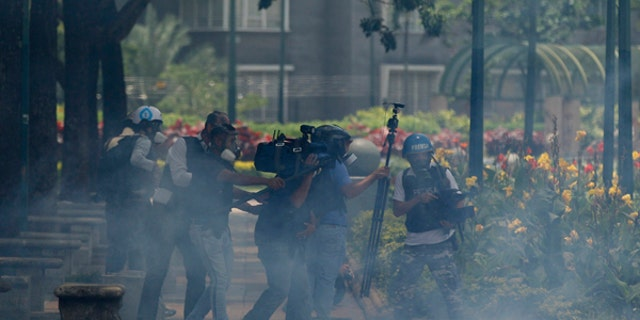 Journalists take cover from tear gas fired at them by the Venezuelan Bolivarian National Guard during clashes at Altamira square in Caracas, Venezuela, Sunday, July 30, 2017. Venezuelans appear to be abstaining in massive numbers in a show of silent protest against a vote to select a constitutional assembly giving the government virtually unlimited powers.