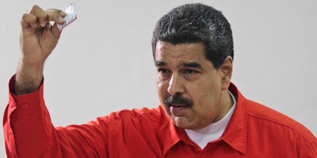 In this photo released by Miraflores Press Office, Venezuela's President Nicolas Maduro shows his ballot after casting a vote for a constitutional assembly in Caracas, Venezuela on Sunday, July 30, 2017.