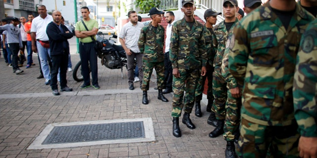 Venezuelan Bolivarian Army soldiers lineup to vote for the constitutional assembly outside of a poll station in Caracas, Venezuela, Sunday, July 30, 2017.