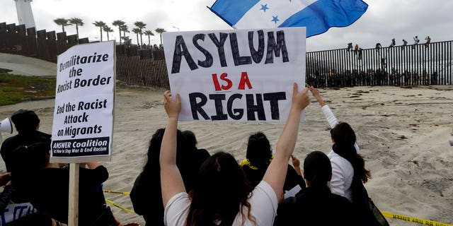 Protesters waving signs amid the arrival of a so-called 'caravan' of asylum-seekers at the US-Mexico border earlier this year.