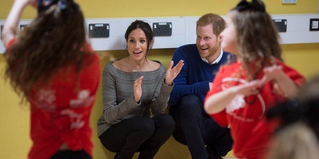 Meghan Markle and Prince Harry watch the Star Hub dancers.