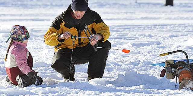Troy Turner, Milford , Maine, and his daughter Kmoi set to work retrieving their ice fishing traps on a cold but sunny day at Pickerel Pond, Milford, Saturday, January 10, 2009.