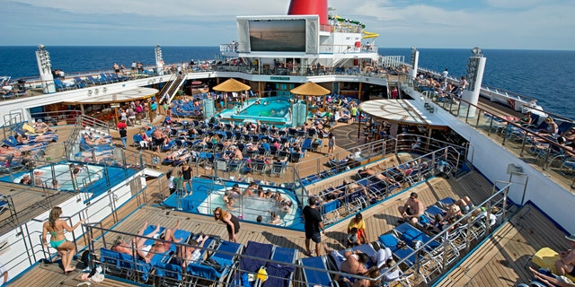 Guests on the Carnival Sunshine soak up the sun on the ship's Lido Deck that features a main pool and two whirlpools. (Andy Newman/Carnival Cruise Lines)