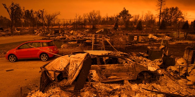 Two vehicles that endured the Carr Fire, one with minor cosmetic damage and one destroyed, rest among leveled homes in the Lake Keswick Estates area of Redding, Calif., on Friday, July 27, 2018.