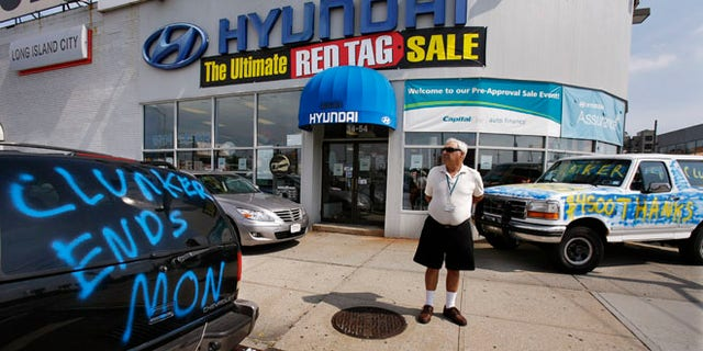 """Aug. 24, 2009: A man looks at a car advertising the last day of the """"Cash For Clunkers"""" auto rebates program outside a Hyundai dealership."""