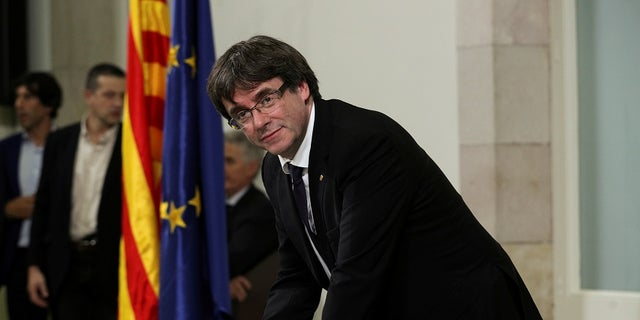 Catalan President Carles Puigdemont signs a declaration of independence at the Catalan regional parliament in Barcelona on Oct. 10.